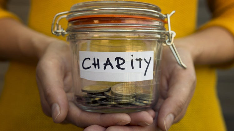 Person holding charity jar with coins