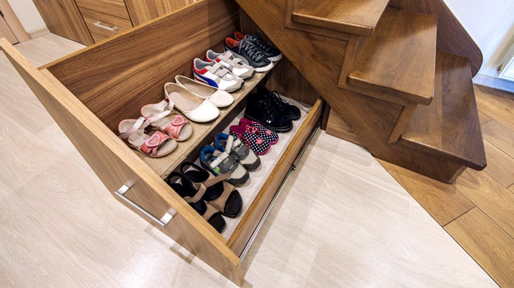 Shoe storage rack under brown wooden stairs