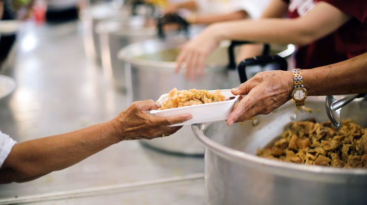 Food in bowl being passed in assembly line