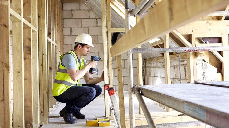Construction worker drilling wooden planks together