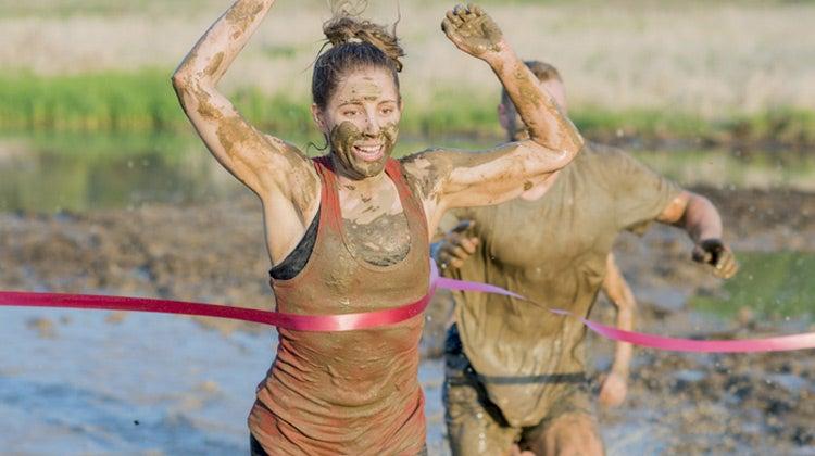Muddy women running across red finish line
