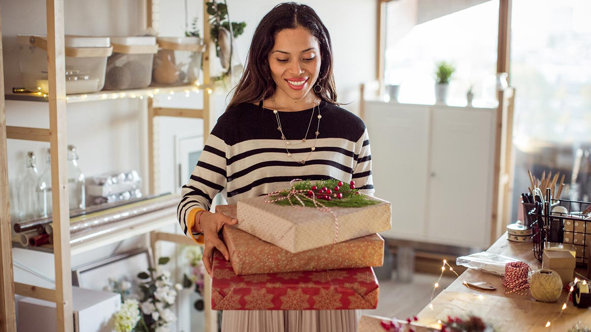 Woman holding stack of presents in a white room
