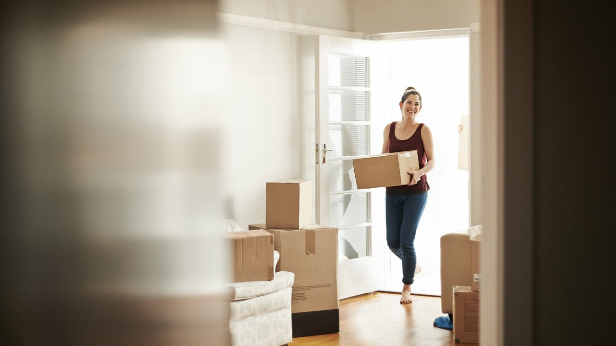 Woman entering room full of moving and packing boxes