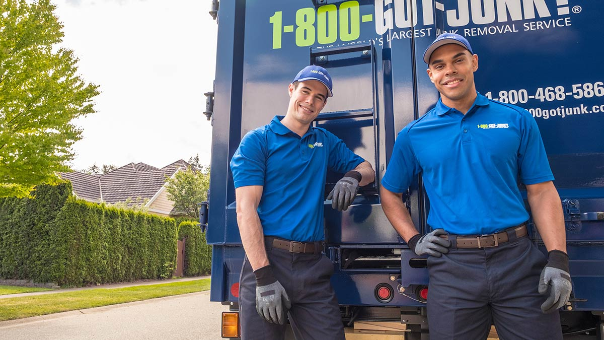 Two TOMs smiling in front of a 1-800-GOT-JUNK? truck