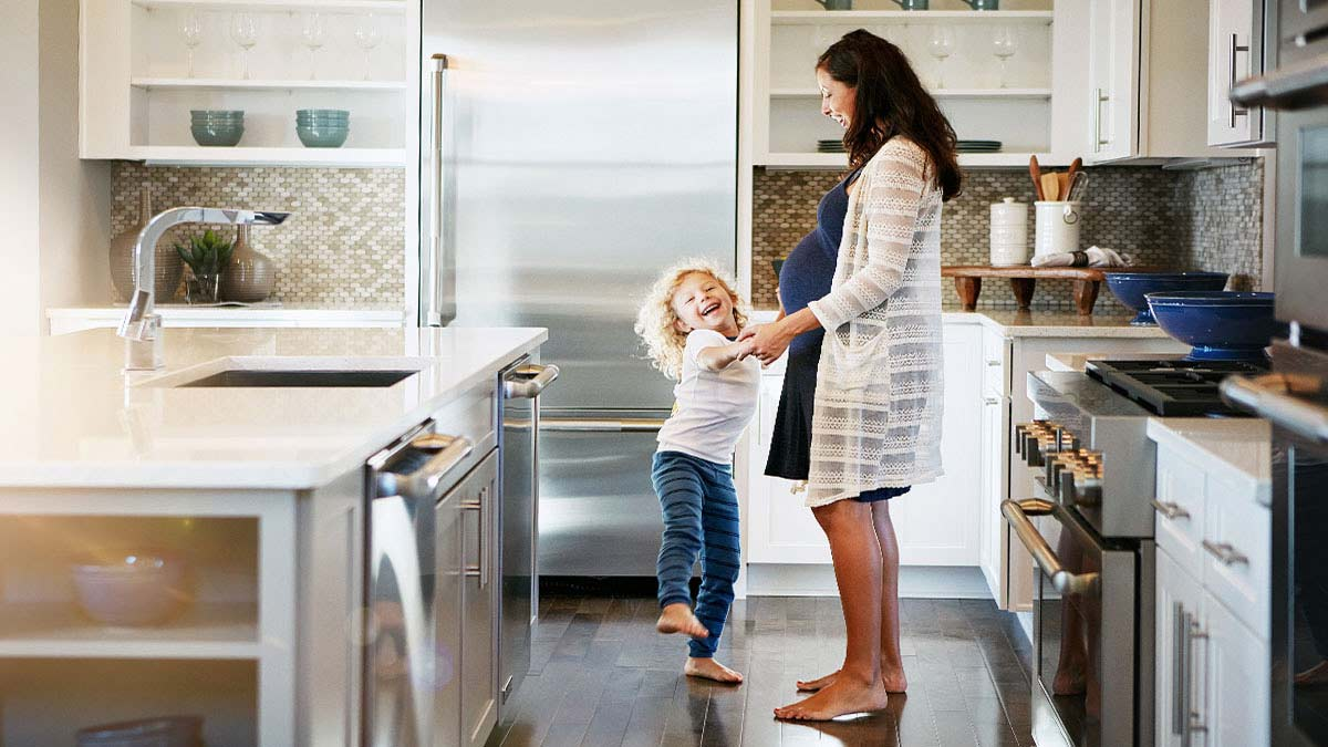 Mother and child dancing in a clean kitchen