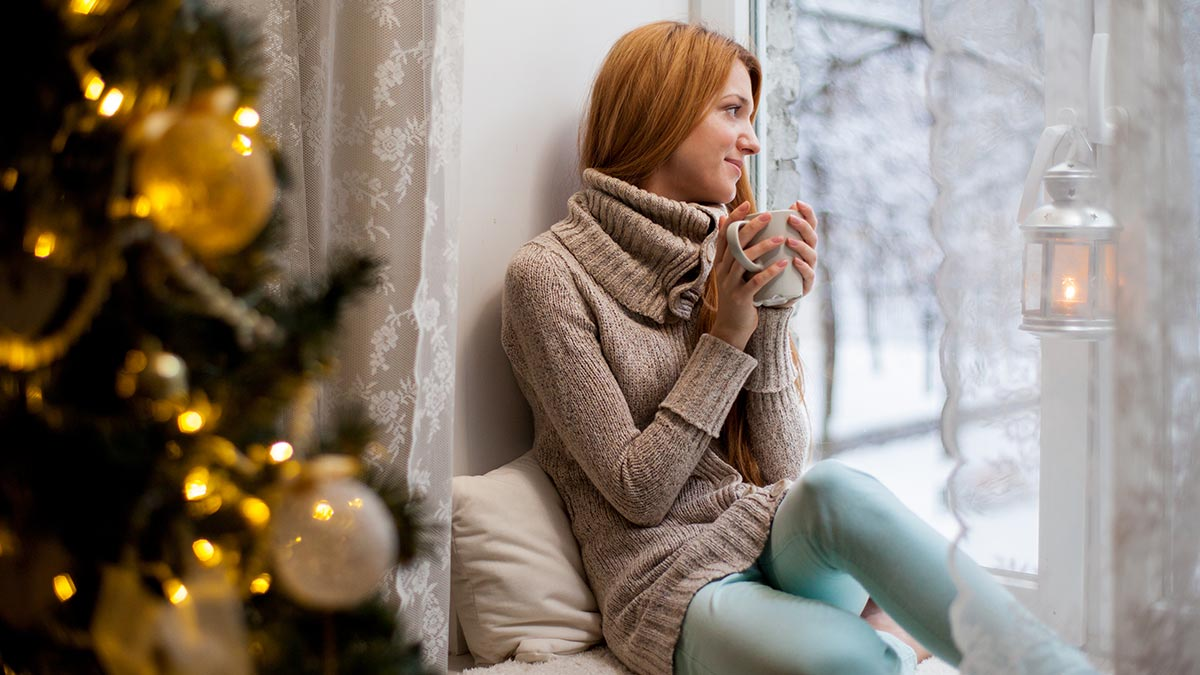 Woman drinking from a mug by the Christmas tree