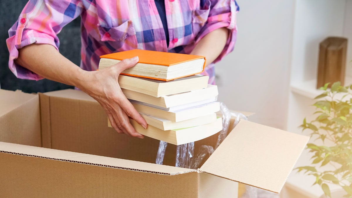 Person putting books in a packing box