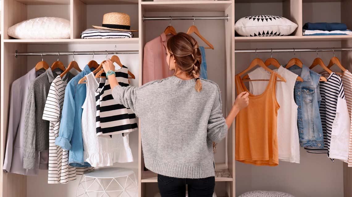 Women organizing her closet with clothes in it