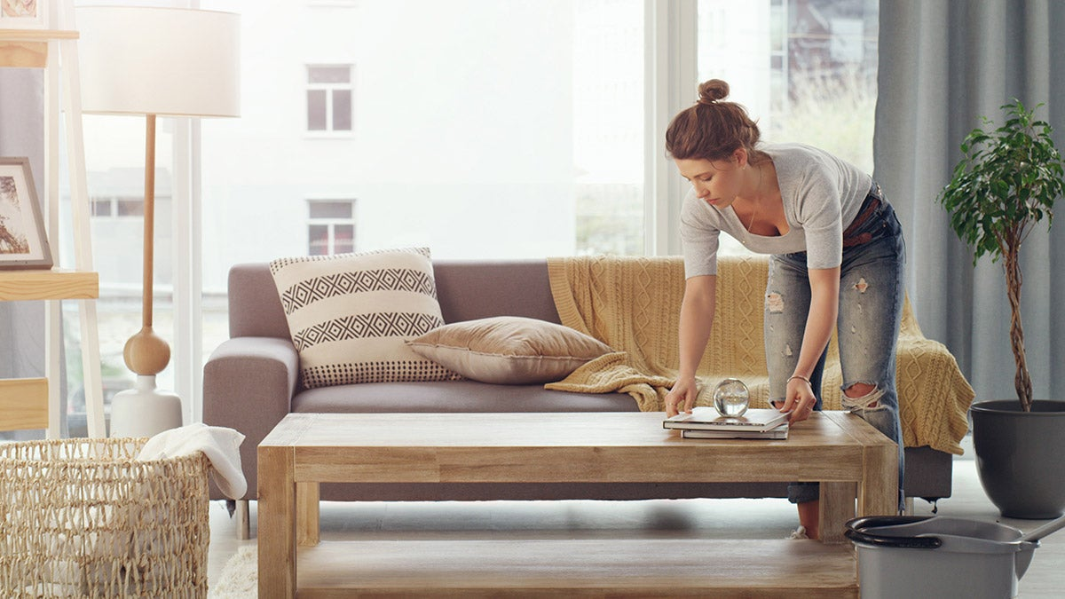 Woman organizing books on a coffee table