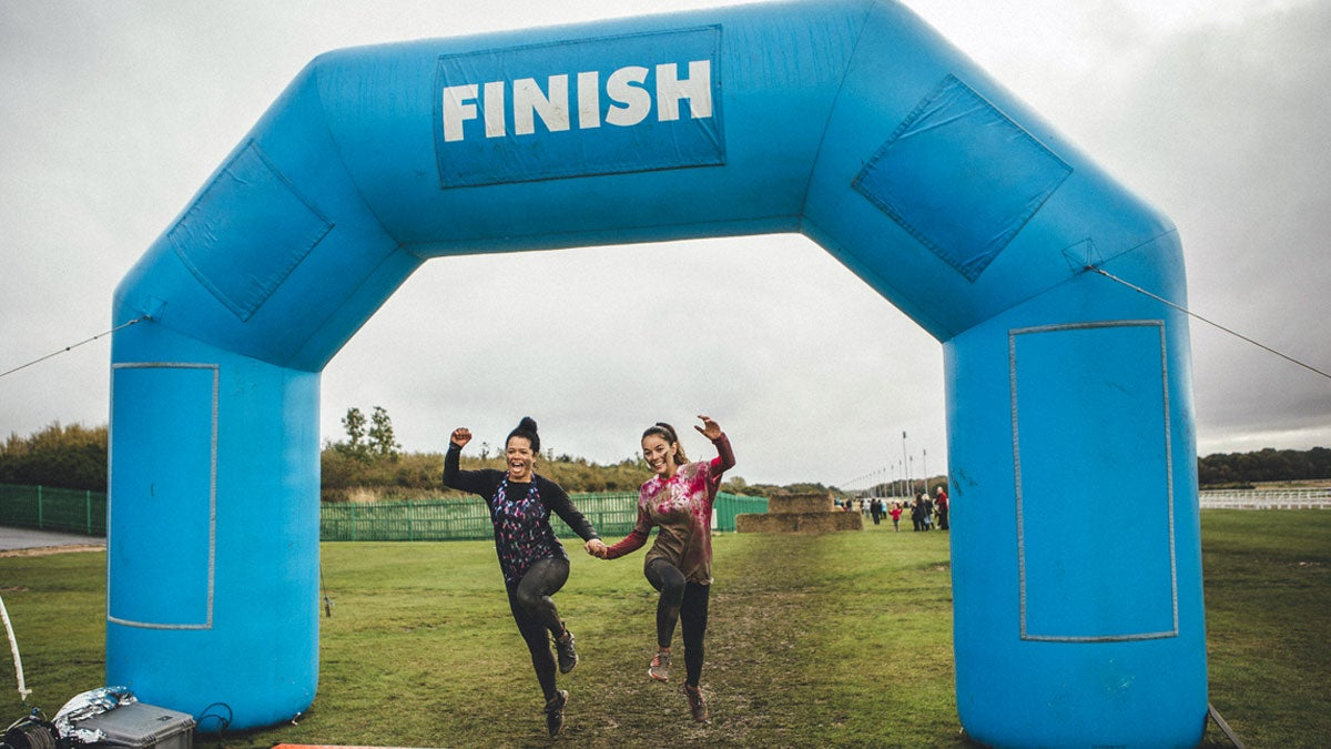Two smiling runners crossing muddy finish line