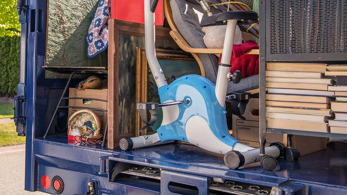 Exercise bike and junk items piled in a large truck