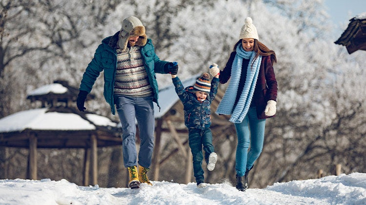 Parents playing with their child in the snow