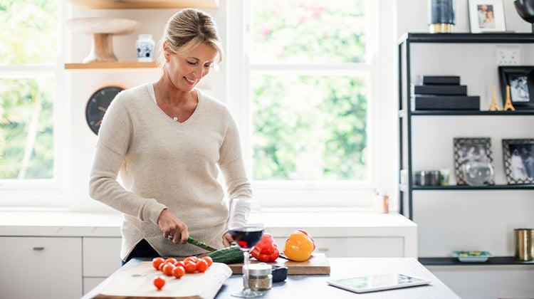 Woman cutting vegetables in her kitchen