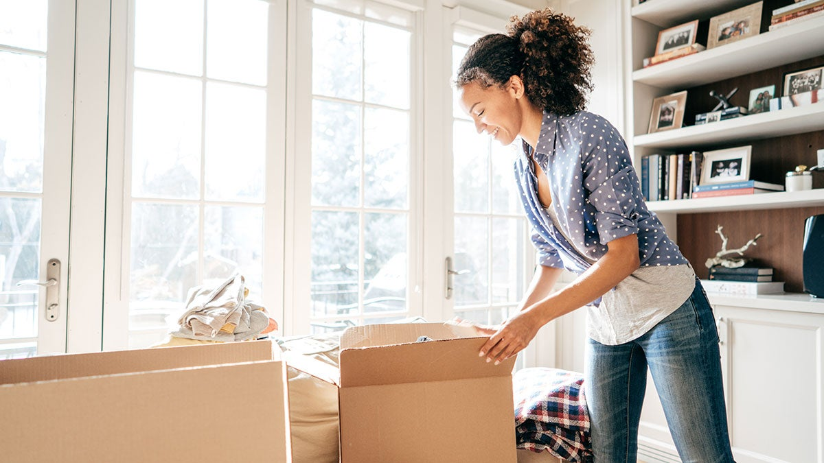 woman packing items in cardboard boxes