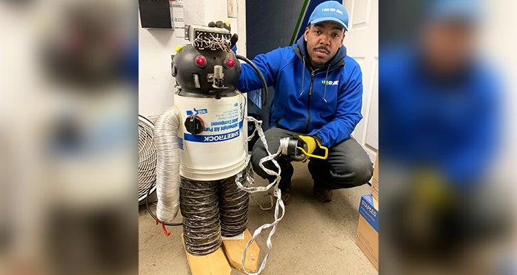1-800-GOT-JUNK? Truck Team Member posing with a homemade robot
