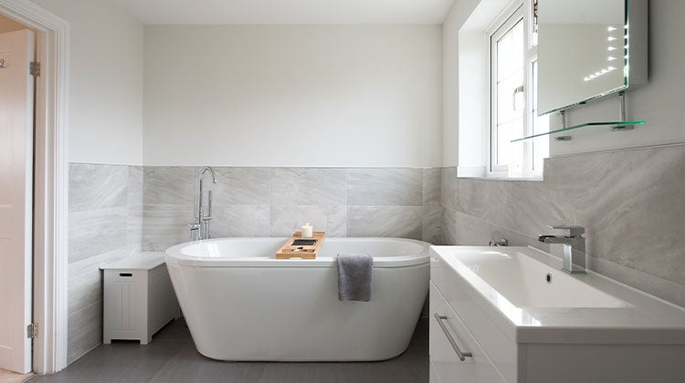 Clean bathroom with grey tiles and a white tub