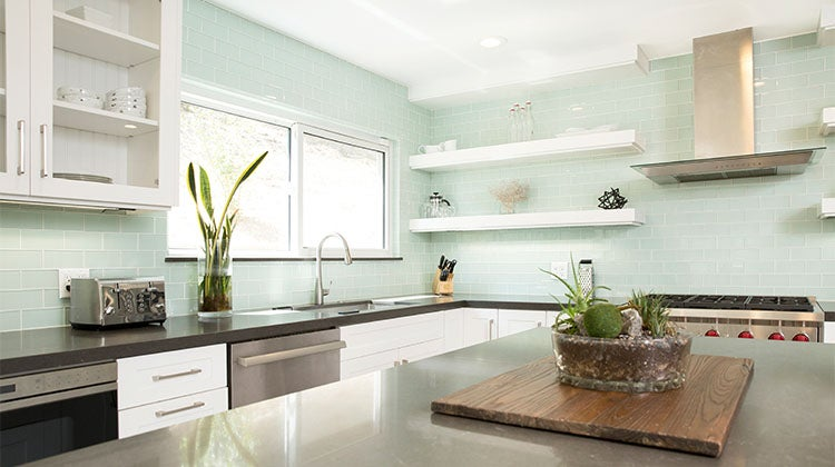 Clean open concept kitchen with blue back splash