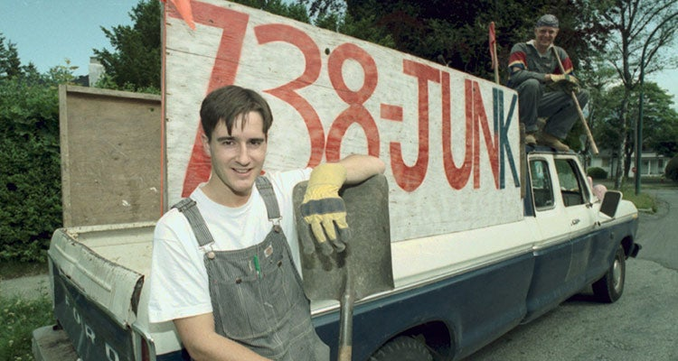 Young Brian Scudamore posing with his first junk truck