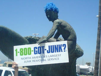 Huntington Beach Surfer wears a 1-800-GOT-JUNK? blue wig