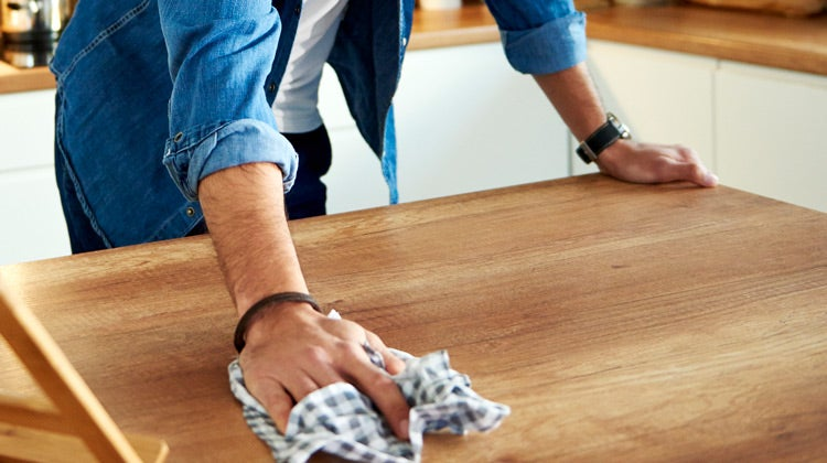 Man wiping a kitchen counter