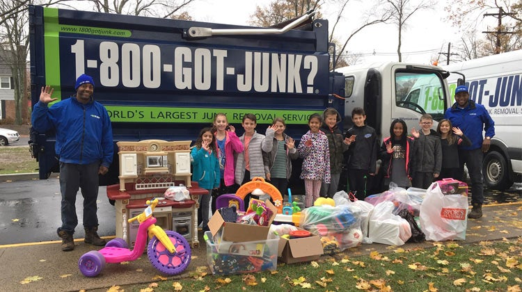 Children with toy donations in front of a 1-800-GOT-JUNK? truck