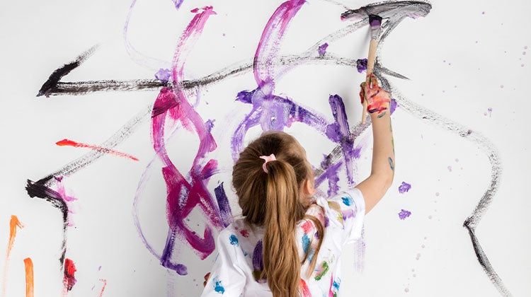 Child painting bright colors on a white wall