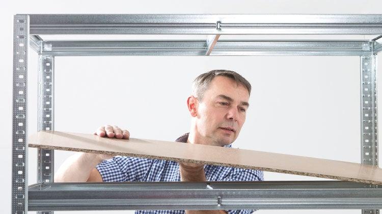 Man installing organizational shelving