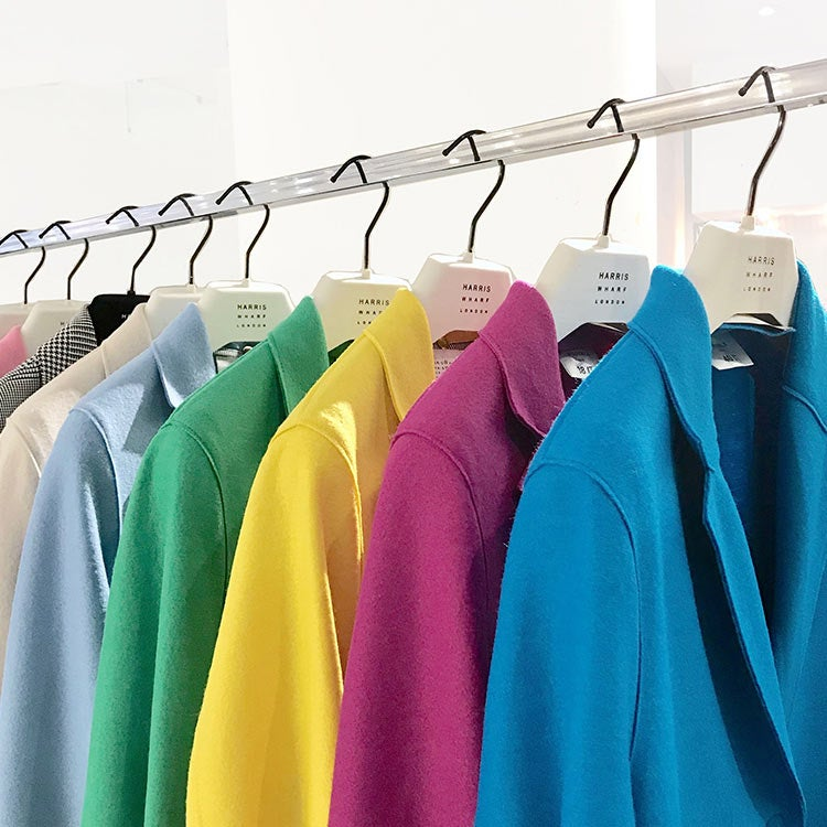 Colorful jackets on white hangers