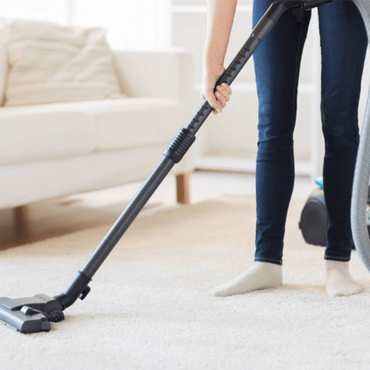Woman vacuuming white carpet