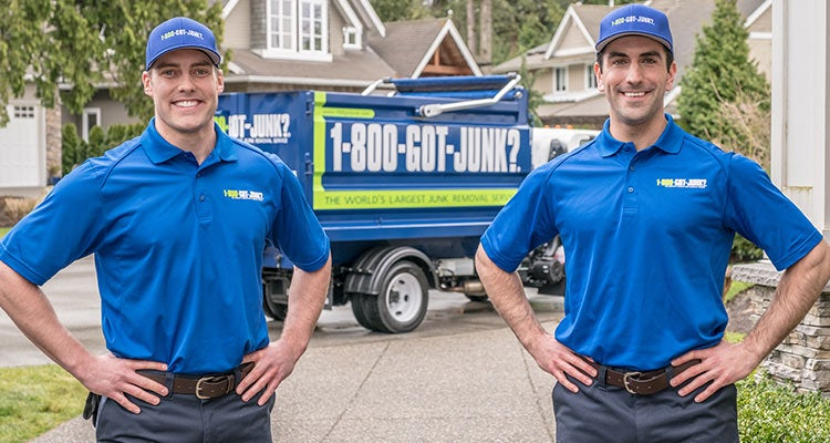 2 TOMs standing in front of a 1-800-GOT-JUNK? truck