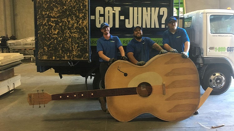 Large acoustic guitar in front of a 1-800-GOT-JUNK? truck