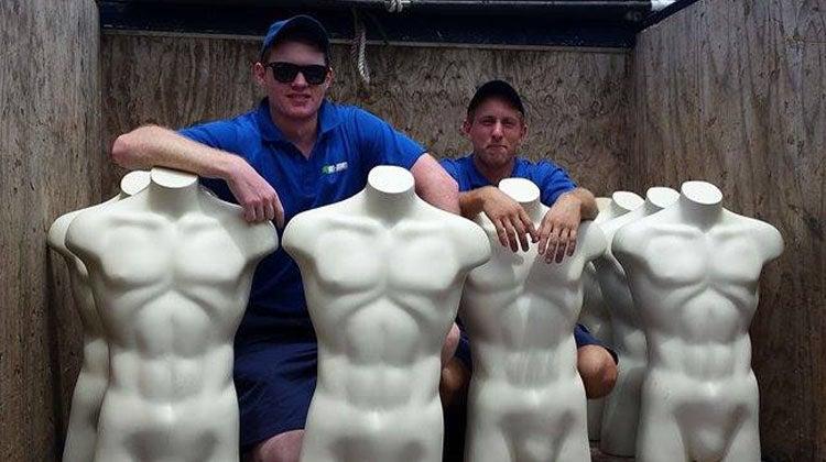 Seven white mannequin torsos in a 1-800-GOT-JUNK? truck